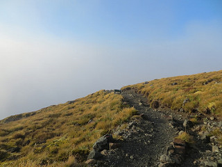 The path of the Kepler over a hill with blue sky peaking through the mist.